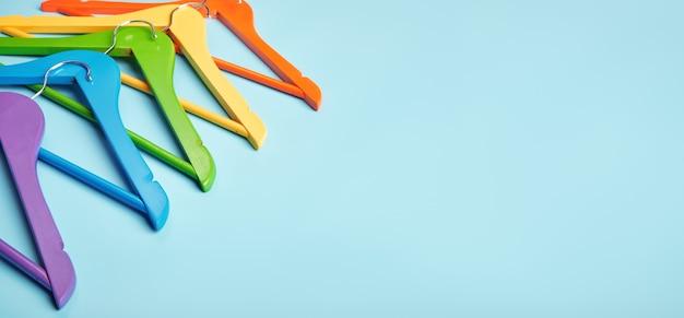 Multi-coloured kleerhangers op een blauwe achtergrond.