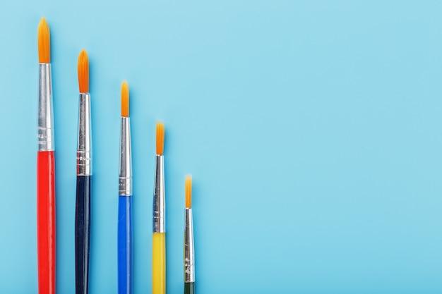 Multi-coloured penselen op een blauwe achtergrond.