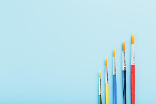 Multi-coloured verfborstels op een blauwe achtergrond.