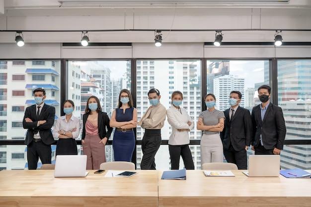 Multi-etnisch business team zelfverzekerd dragen gezichtsmasker staande in de vergaderruimte op coworking space
