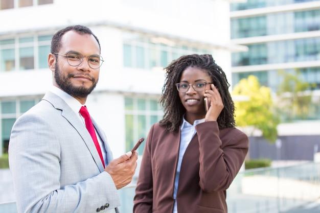 Multi-etnisch commercieel team dat smartphones gebruikt