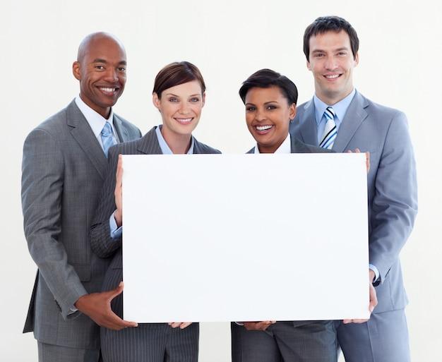 Multi-etnisch commercieel team dat witte kaart houdt