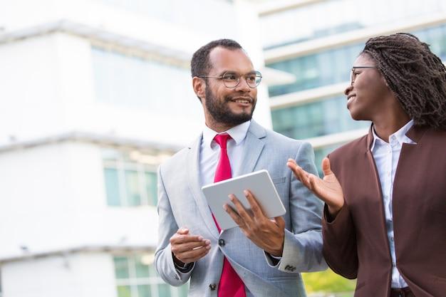 Multi-etnisch commercieel team met tablet die ideeën bespreken