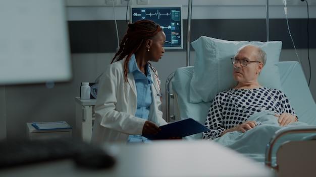 Multi-etnisch medisch personeel legt ziekte uit aan patiënt in ziekenhuisbed bij kliniek zieke oude man...