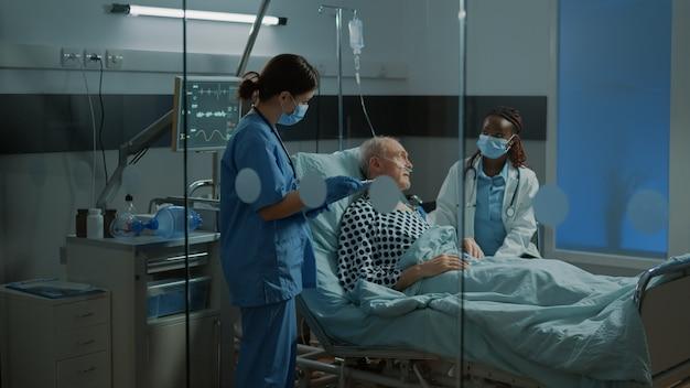 Multi-etnisch medisch personeel praat over de behandeling van de patiënt in het ziekenhuisbed in de herstelfaciliteit ...