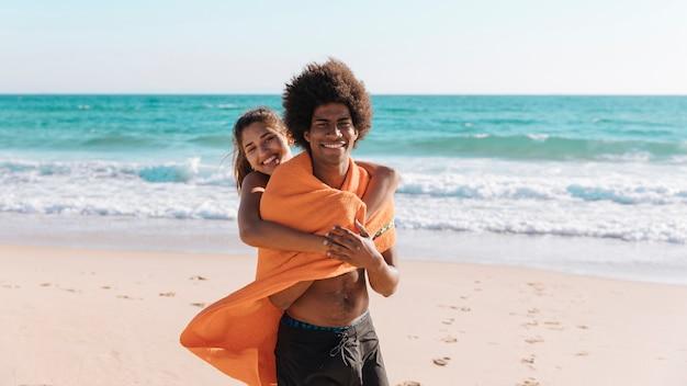 Multi-etnisch paar dat op strand omhelst