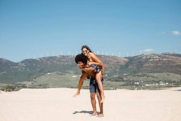 Multi-etnisch paar dat pret op strand heeft