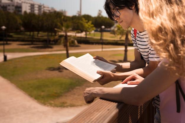 Multi-etnisch paar die op houten omheining leunen terwijl het lezen van boek