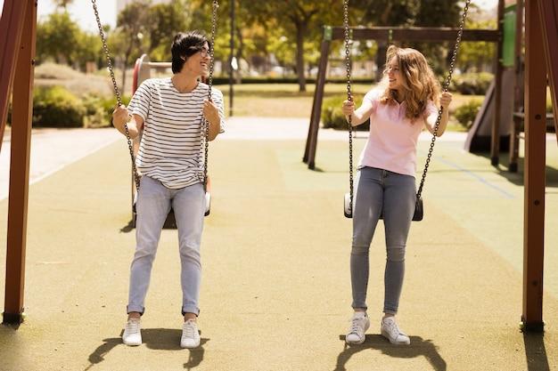 Multi-etnisch paar tieners die op speelplaats slingeren