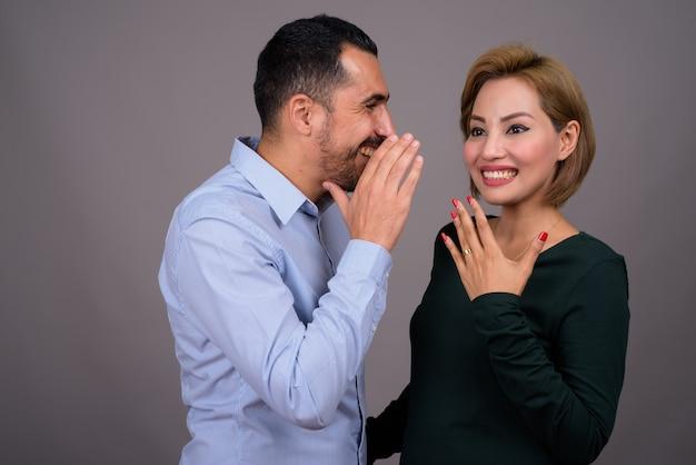 Multi-etnisch paar verliefd tegen grijze muur