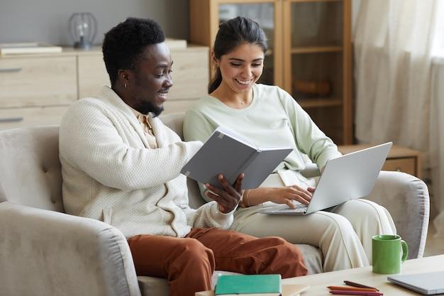 Multi-etnisch paar zittend op de bank leesboek en met behulp van laptop die ze online studeren