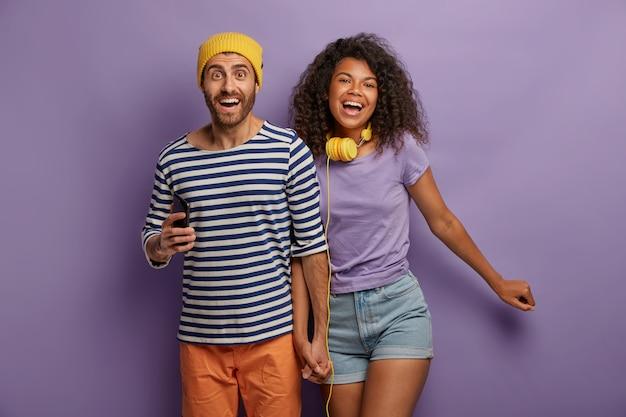 Multi-etnisch stel houdt de handen bij elkaar, lacht vrolijk, geniet van vrije tijd