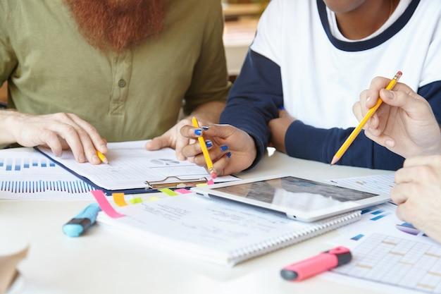 Multi-etnisch team van jonge partners met bijeenkomst in cafetaria, plannen bespreken, ideeën delen, financiële gegevens van project analyseren met behulp van laptop.