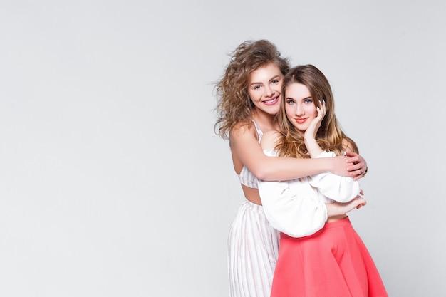 Multi-etnisch vriendschap en ondersteuningsconcept. blanke meisjes in kleurrijke casual kleding knuffelen en plezier maken