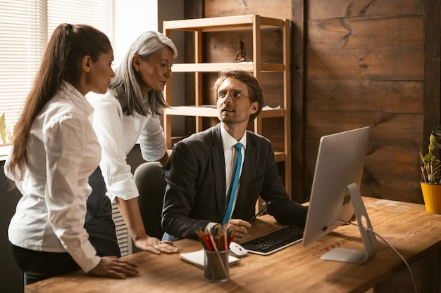 Multi-etnisch zakelijk team van jonge mensen die aan een project werken tijdens zakelijke bijeenkomst, diverse werknemers delen idee met collega's nieuwe updates die hij heeft aangebracht tijdens professionele groepsbriefing. teamwerk concept.