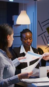 Multi-etnisch zakelijk teamwerk dat managementpresentatie analyseert en financiële grafieken papierwerk deelt