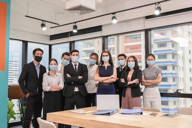 Multi-etnisch zelfverzekerd commercieel team dat zich met gekruiste wapens bevindt en medisch masker draagt in nieuw normaal bureau