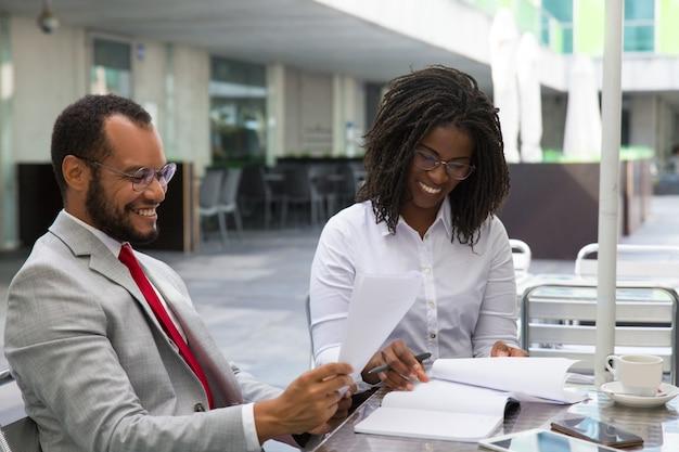 Multi-etnische bedrijfscollega's die rapporten bestuderen