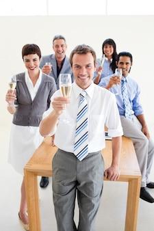 Multi-etnische bedrijfsmensen die met champagne roosteren