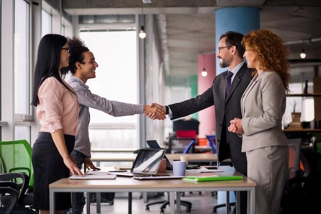 Multi-etnische bedrijfsteams bij vergaderzaal die handen schudden.