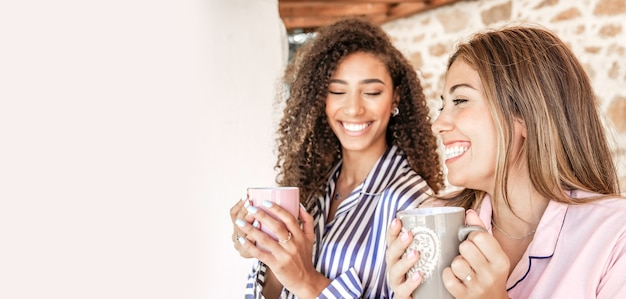 Multi-etnische beste vrienden vrouwen in pyjama glimlachend met een kopje thee met witte kopie ruimte aan de linkerkant - concept: blijf thuis en geniet van je leven