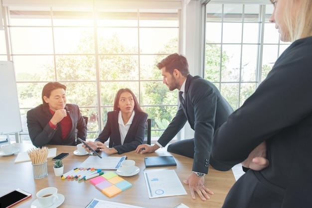 Multi-etnische collega kijken naar tablet die zakenvrouw tonen aan haar collega op kantoorvergadering.