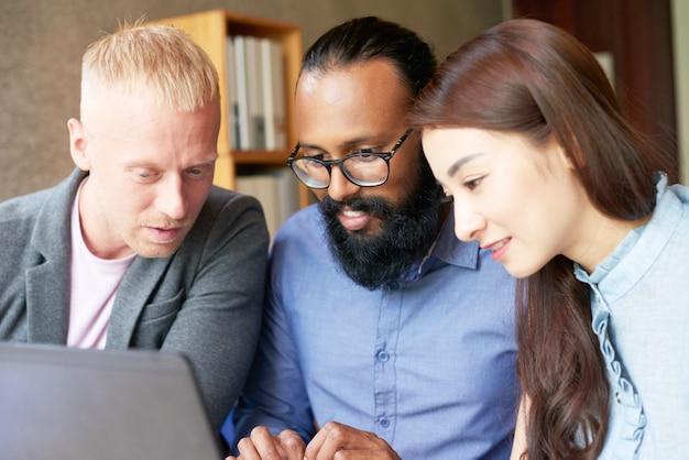 Multi-etnische collega's die aan laptop in bureau samenwerken en het scherm bekijken