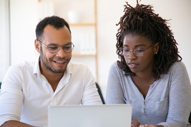 Multi-etnische collega's die laptop met behulp van