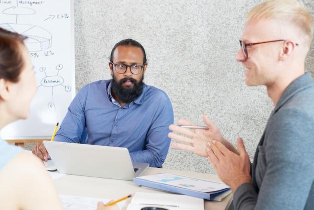 Multi-etnische collega's die op het werkvergadering samenwerken in bureau