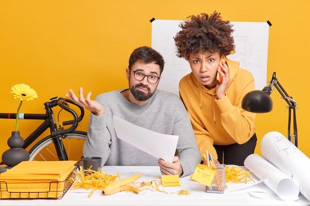 Multi-etnische collega's poseren in een modern kantoor en proberen het ontwerpproject af te ronden. aarzelende man houdt papier haalt zijn schouders op met een onwetende uitdrukking. afro-amerikaanse vrouw probeert baas te helpen praten via telefoon