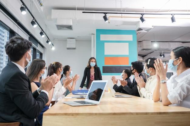 Multi-etnische collega's vieren met applaudisseren de vrouwelijke stafmedewerker tijdens bijeenkomst in nieuwe normale kantoor