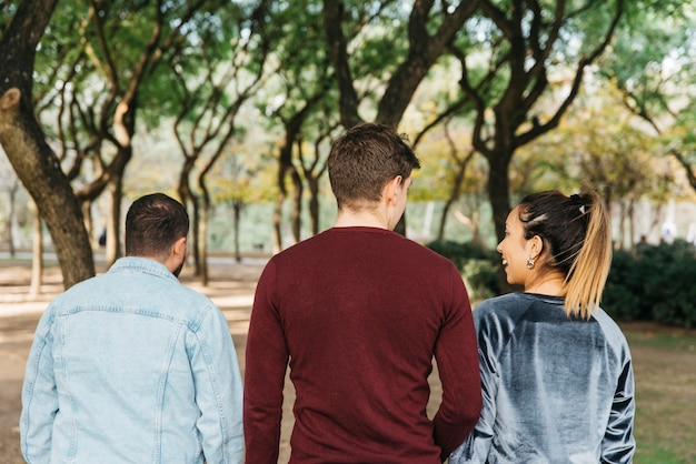 Multi-etnische glimlachende vrienden die in park lopen en pret hebben