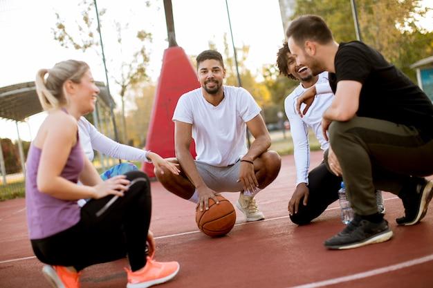 Multi-etnische groep basketbalspelers die op hof rusten