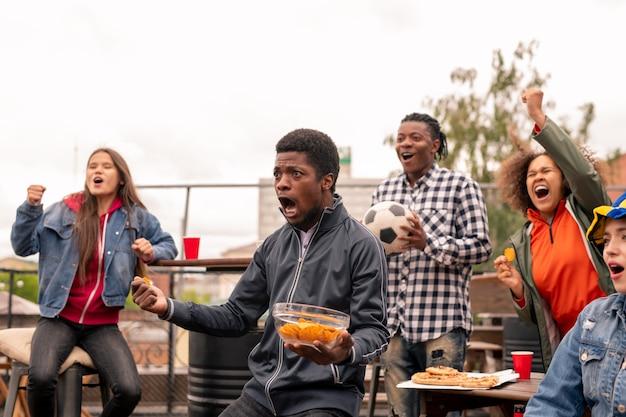 Multi-etnische groep extatische jongeren met een snack die schreeuwt tijdens het kijken naar voetbaluitzendingen buitenshuis