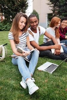 Multi-etnische groep gelukkige jonge mensen die boek lezen en laptop op gazon buitenshuis gebruiken