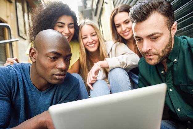 Multi-etnische groep jonge mensen die naar een tabletcomputer kijken