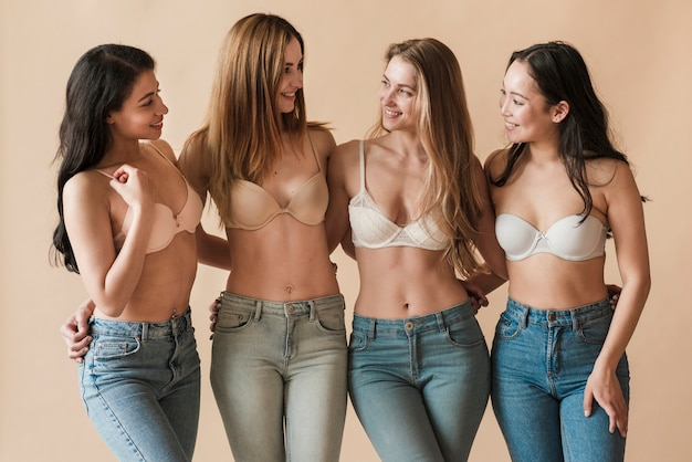 Multi-etnische groep jonge vrolijke meisjes die bustehouders en het omhelzen dragen