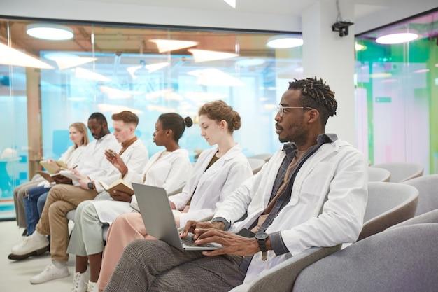 Multi-etnische groep jongeren die laboratoriumjassen dragen en aantekeningen maken terwijl ze binnen zitten tijdens een lezing over geneeskunde op de universiteit, kopieer ruimte