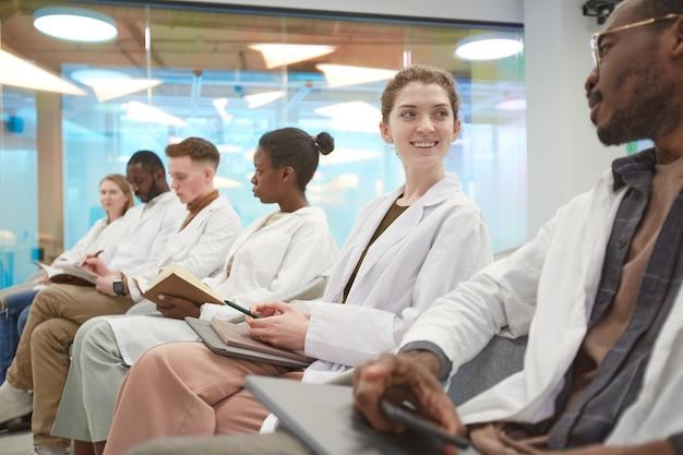 Multi-etnische groep jongeren die laboratoriumjassen dragen en glimlachen terwijl ze in de rij zitten en tijdens een lezing over geneeskunde op de universiteit, kopieer ruimte