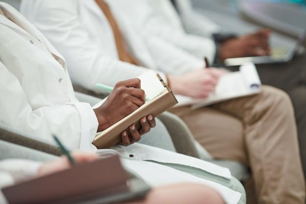 Multi-etnische groep jongeren die laboratoriumjassen dragen terwijl ze in de rij in het publiek zitten en aantekeningen maken in een lezing over geneeskunde, kopieer ruimte