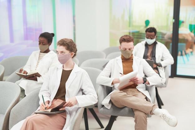 Multi-etnische groep jongeren die maskers en laboratoriumjassen dragen terwijl ze luisteren naar een lezing over medicijnen op de universiteit of een coworkingcentrum, kopieer ruimte