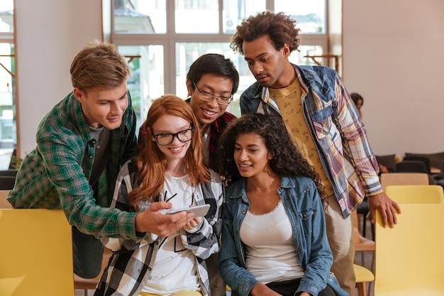 Multi-etnische groep jongeren die samen zitten en mobiele telefoon gebruiken