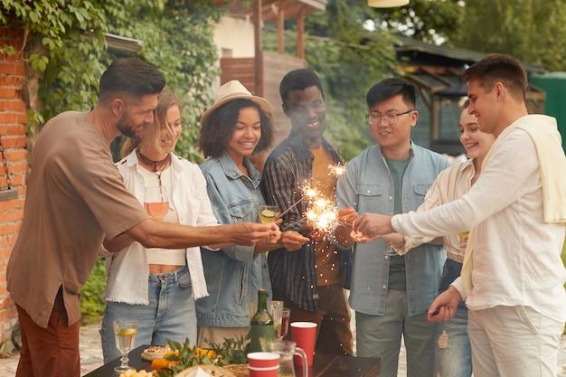 Multi-etnische groep jongeren die wonderkaarsen aansteken terwijl ze genieten van zomerfeest op buitenterras