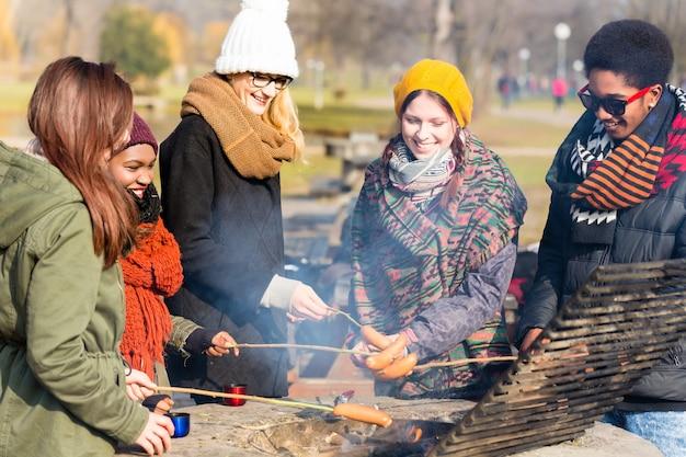 Multi-etnische groep jongeren die worstjes buitenshuis roosteren in een koude dag van de herfst