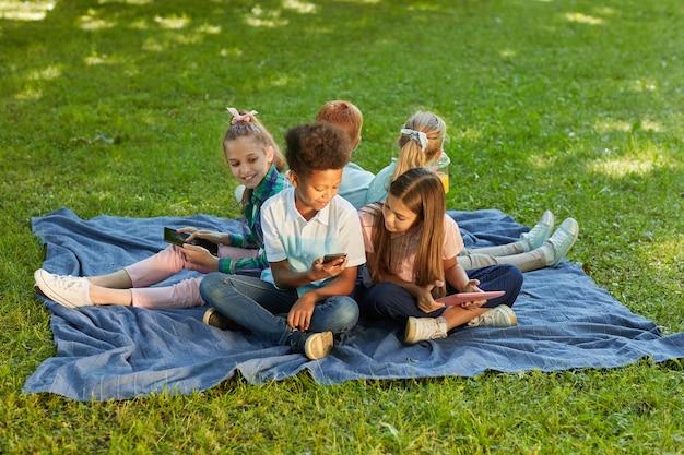 Multi-etnische groep kinderen met behulp van gadgets zittend op groen gras in park buiten