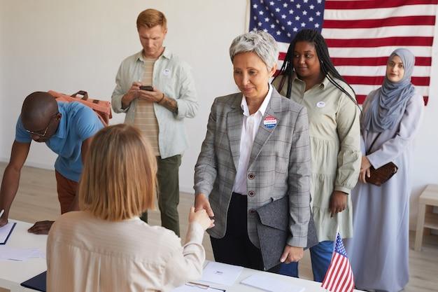 Multi-etnische groep mensen bij het stembureau versierd met amerikaanse vlaggen op verkiezingsdag, focus op lachende senior vrouw handen schudden met stemmend ambtenaar, kopie ruimte