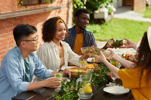 Multi-etnische groep mensen die eten delen terwijl ze genieten van een diner met vrienden en familie buiten op zomerfeest