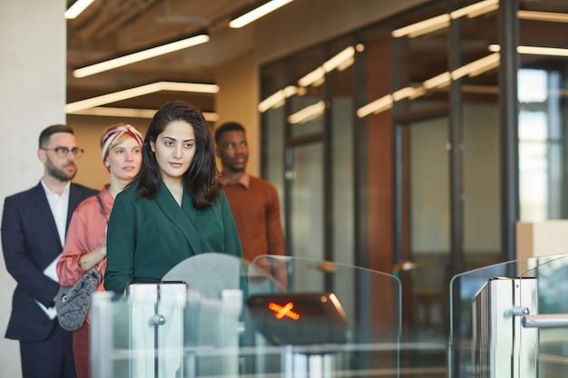 Multi-etnische groep mensen die in de rij staan terwijl ze geautomatiseerde poort passeren om het kantoorgebouw binnen te gaan, focus op jonge midden-oosterse vrouw die identiteitskaart veegt, kopie ruimte