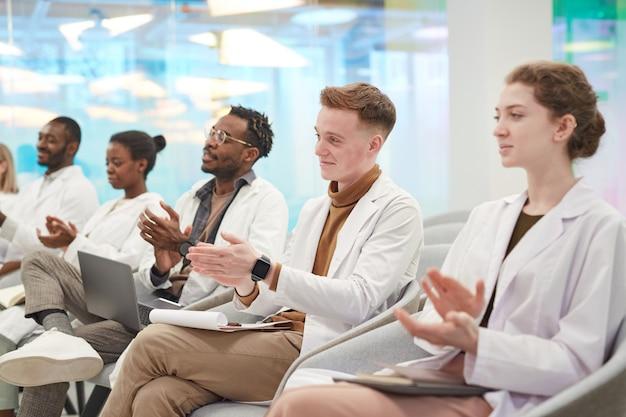 Multi-etnische groep mensen die laboratoriumjassen dragen die in de rij in het publiek zitten en applaudisseren op medisch seminar, kopieer ruimte