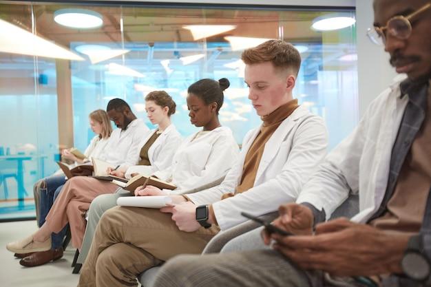 Multi-etnische groep mensen die laboratoriumjassen dragen terwijl ze in de rij zitten en aantekeningen maken tijdens de lezing over geneeskunde op de universiteit, kopieer ruimte